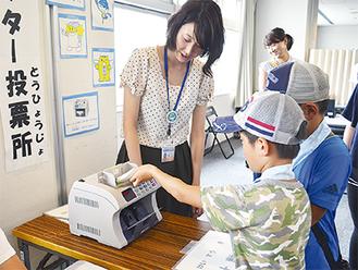 投票用紙の計数器を体験する子どもたち