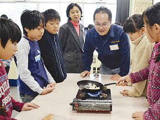 児童と柿の種づくりをする小森さん(右から3人目)