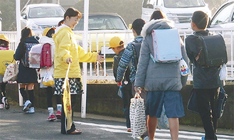 田中さんが差し出した手に、通り過ぎる子どもたちが次々とタッチしていく