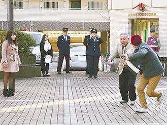 目撃者役の学生(左)と事件を演じる警察関係者ら