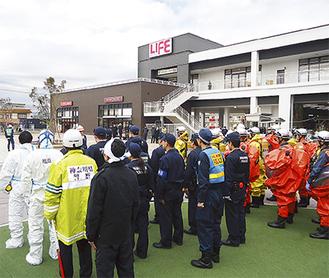 検挙担当の警察官とオレンジ色の防護服姿の消防署員