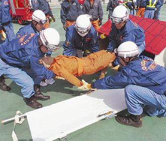 要救助者を模した人形を救出する消防団員