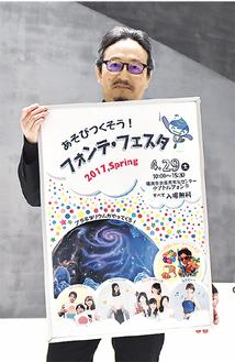 イベントの告知ポスターを持つ二村館長