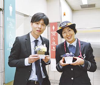 作品を手にする関代表(左)と中野駅長