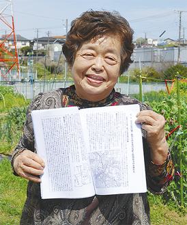 校正中の冊子を手に笑顔を見せる翠川さん