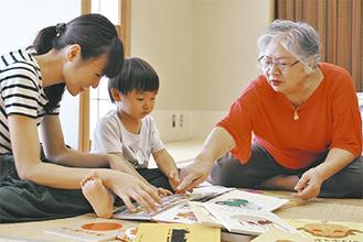 絵本に親しむ親子と高見眞理子代表(右)