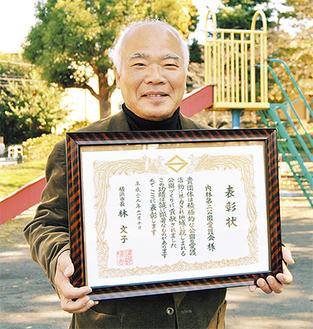 表彰状を手に公園に立つ前田会長