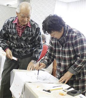 絵付けのアドバイスをする山村さん(左)