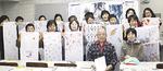 山村さん親子と完成した作品を掲げる参加者ら