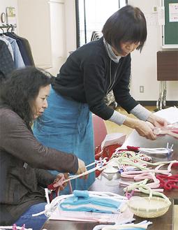 ぞうりを作る参加者と塚本さん(右)