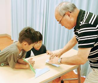 子どもたちに折り紙を教える永田さん