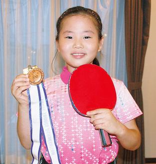 メダルを手に笑顔の廣田さん