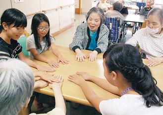 学校で流行の手遊びを教える児童たち