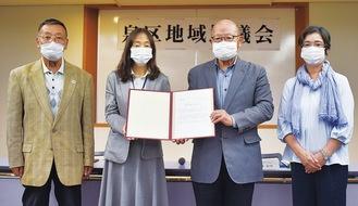 課題検討依頼書を手にする深川区長(中央左)と協議会の松浦会長(中央右)