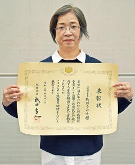 表彰状を持つ町田さん