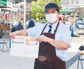 GoTo事業で実施中のイベントチラシを持つサンモール洋光台の会長
