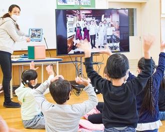 画面越しに手を振り合う伊勢山小の児童と社員たち