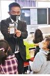 児童たちにアプリストアの画面を見せる藤井教諭