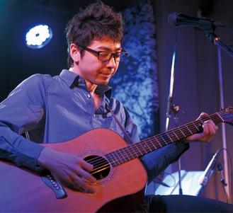 ライブでギターを弾くオオゼキさん