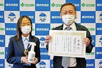 除菌剤を持つ深川区長(左)と区からの感謝状を受け取った平井社長