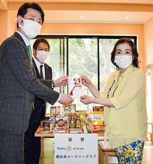 目録を渡す飯田会長(左)