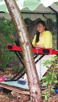 木々に囲まれ演奏する丹生谷さん=本人提供