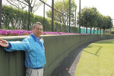 外野フェンス際の芝桜を紹介する田村所長