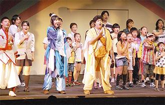 1月15日の初演で歌とダンスを披露するメンバーたち