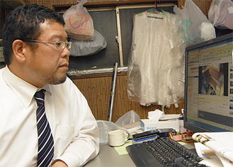 被災地で撮影した現地の人の姿に見入る北井さん(4月14日、事務所で)