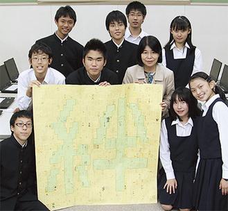 唐桑中へのメッセージが書かれた「絆」を手に、同校生徒会と鷲尾校長(10月25日、同校で)