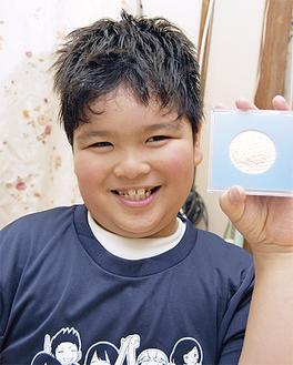 金メダルを手にする小石君