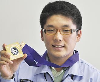 金メダルを手にする岡田さん
