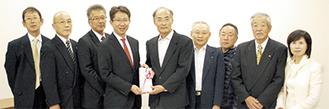 鈴木太郎会長(中央左)から十愛療育会の岸本孝男理事長(中央右)に米120kgの目録が贈呈された