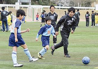 笑顔でボールを追いかける子どもと大学生