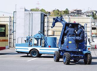 バス車両から運び出した不審物を爆発物処理筒車(中央)に運ぶ