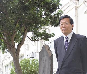 伊藤法彦校長。背景の同小中庭にある樹木は、明治天皇の皇女である泰宮と富美宮が植樹したもの