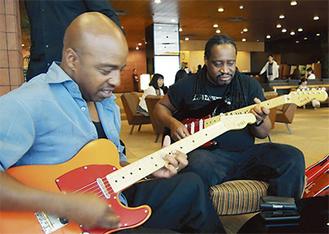 寄贈されたギターを奏でるムーア氏(左)