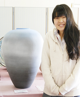 作品の前で笑顔を見せる森田さん