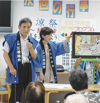 自作の紙芝居を披露する中島さん(左)