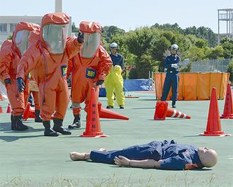 化学防護服を着用し、救出に向かう隊員