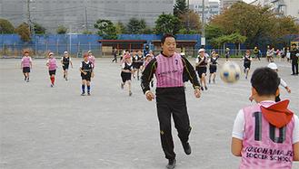 児童とサッカーをする奥寺さん