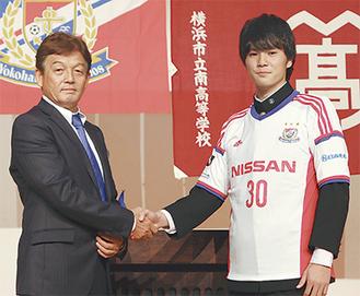 マリノスの下條本部長(左)と握手を交わす田口さん
