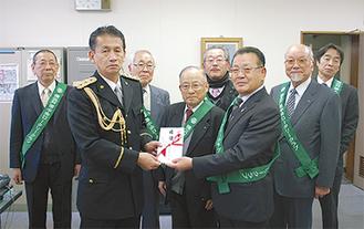 田口署長(左から2番目)に目録を手渡す鈴木会長(右から3番目)