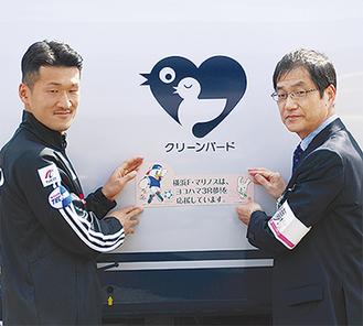 車両にマグネットを貼る葛西局長(右)と富澤選手