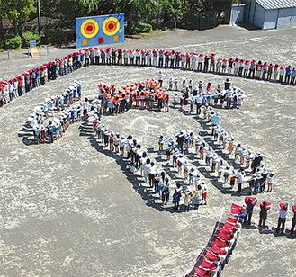 児童が並んで表現した同校マスコット、うさぎの「またピョン」を、地域住民らが「ハート」で囲んだ(写真上が正面)