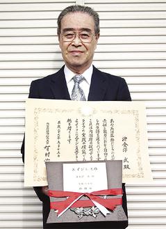 盾と賞状を手に笑顔の津金澤さん