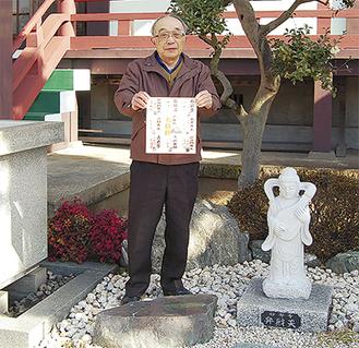 妙秀寺境内で色紙を手にする事務局長の櫻井英彦さん