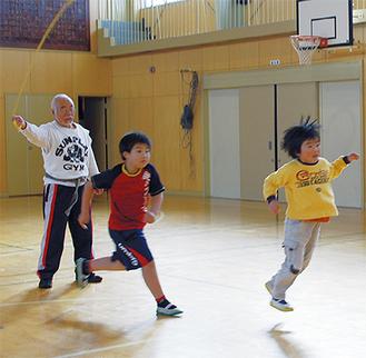 竹中さん(左)が回すロングロープに飛び込む児童ら