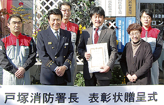 賞状を手にする坂本代表取締役と(中央右)と坂本署長(中央左)