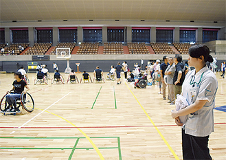車椅子バスケットボールコーナーで安全の見守りをする学生(右)